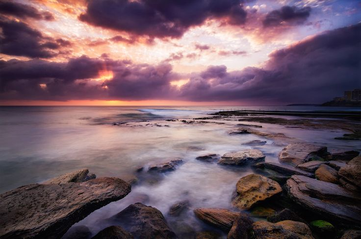Dramatic skies and waves breaking are a highlight of Cronulla Beach and the adjacent ocean pools for photographers. As the sun has just risen and is hiding behind a cloud bank, this created the dramatic sky with a little bit of sun rays breaking through the clouds. A very picturesque place to live and take photos.