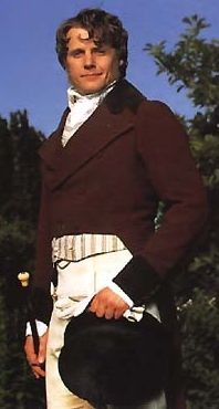 Colonel Fitzwilliam is sporting a style very similar to the above, particularly in the cut of the jacket. The contrasting velvet trim is something that became more and more popular into the late Regency. The only thing that seems a little odd to me is the pointed detail of his waistcoat. Generally the cut of the waistcoat was straight across, and only about two inches showed, not four as here. Still, the feel is captured, down to the hairstyle and the gloves, hat, and cane.