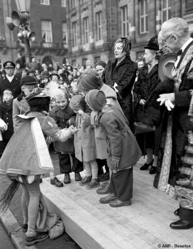 Koningin Juliana en de prinsesjes op de Dam met zwarte Piet die pepernoten uitdeelt