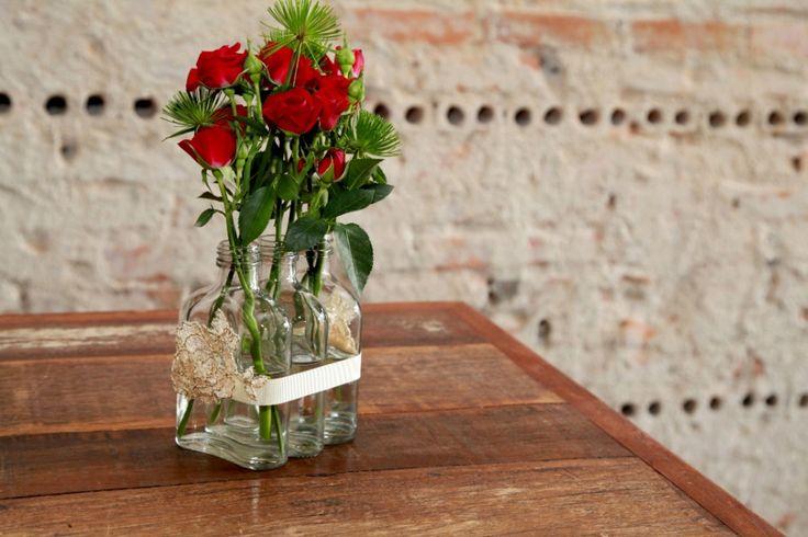 """1. Garrafas de uísque e rosinhas vermelhas compõem arranjo delicado. Os floristas Marcia Sorgenfrei e Rodrigo Carneiro, da Agapanthus Floricultura, em Curitiba, te ensinam a criar um arranjo delicado e vistoso com garrafinhas individuais de uísque e rosas """"spray""""; acompanhe o passo a passo e faça o seu!  Fotografia: Andre Gruby/ Divulgação."""