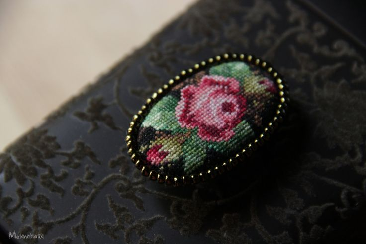 Charming oval brooch handcrafted in the old style.  Handmade micro cross-stitch with cotton mouline thread framed by seed beads. Back is lined with natural leather.  Dimensions: 5 * 3 cm
