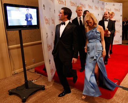 Cast members Jon Hamm and January Jones walk off the photo room stage while watching Slumdog Millionaire win best motion picture drama on a monitor in the photo room at the 66th annual Golden Globe Awards at the Beverly Hilton Hotel in Beverly Hills in January, 2009.