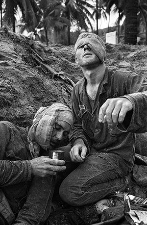 A US medic looks up with his one uncovered eye as he continues to treat a wounded comrade. U.S. 1st Cavalry Division medic Thomas Cole, from Richmond, Va., looks up with his one uncovered eye as he continues to treat wounded Staff Sgt. Harrison Pell during a January 1966 firefight in the Central Highlands between U.S. troops and a combined North Vietnam- ese and Viet Cong force. Photograph: Henri Huet/AP