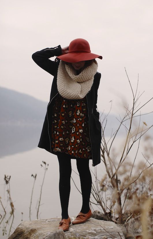 Love these autumnal photos, with the darker substantial autumn and winter colors against the dun colors of a sleeping earth.  Great burnt orange hat and shoesies with the dark coat and opaque tights and big bukly neck wrap in bisque. Great photo!