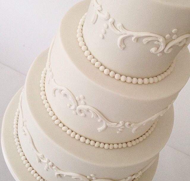 Classic white wedding cake with scroll detailing.