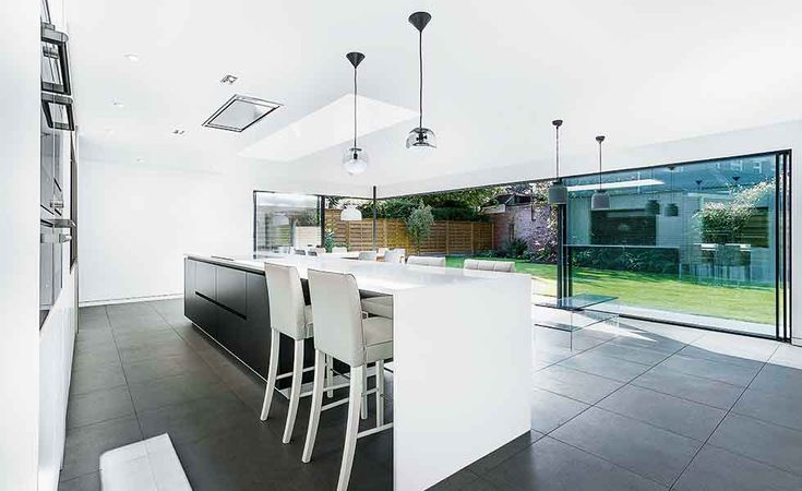 White units with black tiles contrast in this contemporary kitchen in Hampshire
