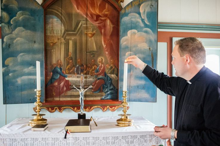 Pastor pall Agust Olafsson lights candles at Budir Church, Iceland