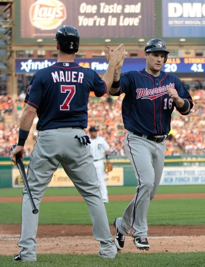 Josh Willingham #16 of the Minnesota Twins scores on a single to left field by Trevor Plouffe #24 and is congratulated by Joe Mauer #7 during the fourth inning of the game against the Detroit Tigers at Comerica Park on July 2, 2012 in Detroit, Michigan