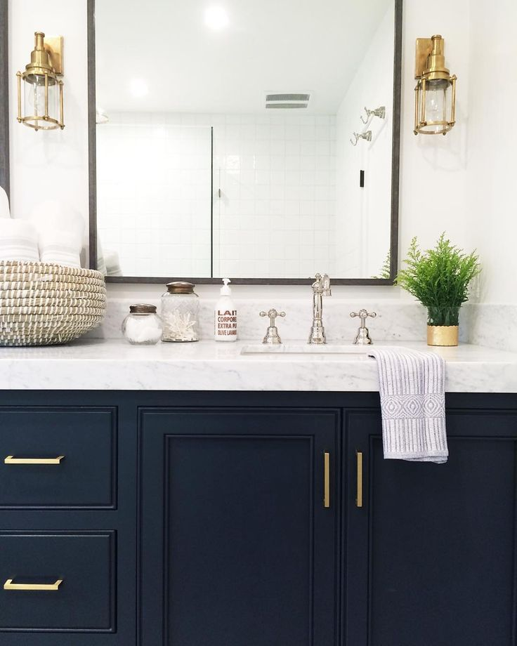 Bathroom With Navy Cabinets Marble Countertops And Gold Light Fixtures And Pulls