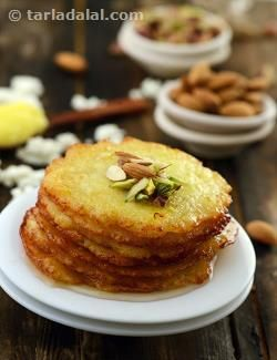 Delicate and lacy malpuas made using fresh paneer which will melt in your mouth. This recipe is somewhat comparable to the famous malai malpuas of pushkar near ajmer. Serve them warm topped with rabri or just garnished with chopped almonds and pistachios. You will find chenna malpuas only at a few cities in rajasthan. Just grab the opportunity to make them as they are simply divine! these malpuas are a little tricky to make, so be patient. Sometime, they can just disintegrate in the ghee ...