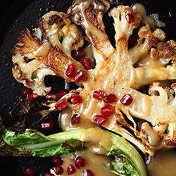 Stek z kalafiora podawany z sosem tahini i owocem granatu. Stek z kalafiora, w środku idealnie miękki, na zewnątrz chrupiący.