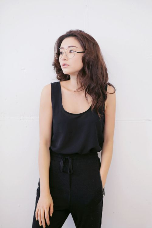 Fashion. Black. Asian. Wavy hair. Round glasses. Sleeveless. This looks like a jumpsuit but I don't really know.