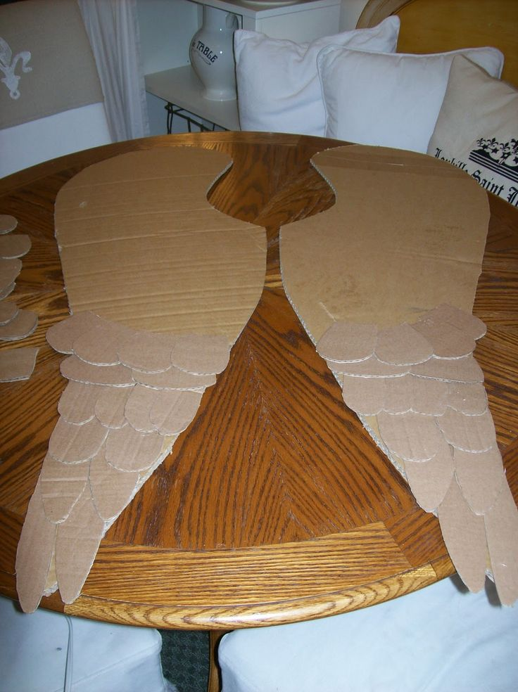 "DIY Cardboard Angel Wings...she drew an angel wing on one side of a large box and traced a matching wing on the other side, cut them both out and then started cutting out the ""feathers"" from additional cardboard boxes. Many.....Many.....Many feathers later she painted them."