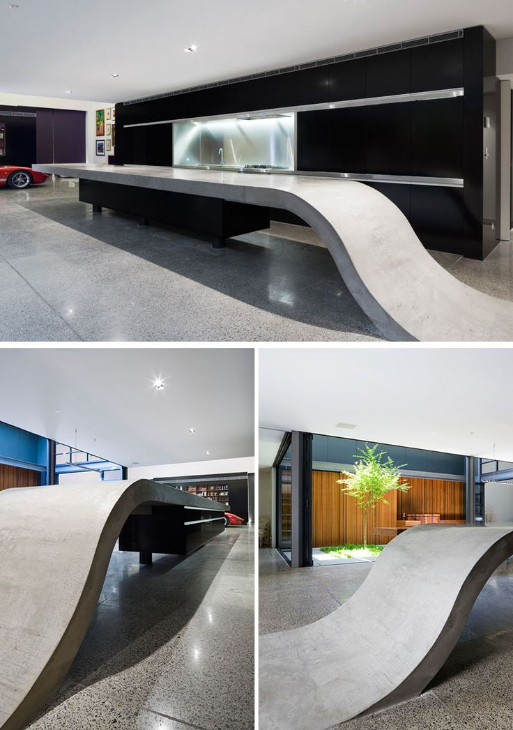 11 Creative Concrete Countertop Designs To Inspire You |  The 9 meter long concrete countertop in the kitchen of this home rises up from the floor to create a sculptural kitchen island.
