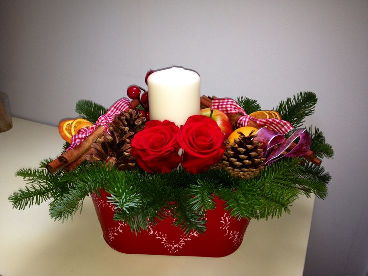 Red roses cinnamon sticks scented cones and berries make the perfect table arrangement