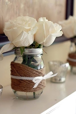 Jute twine and ribbon wrapped mason jars with ivory roses. Rustic and elegant decorating