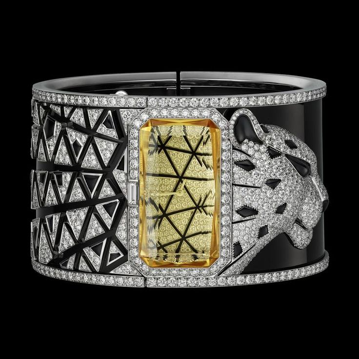 Cartier Panthere Astrale cuff watch in white gold, black onyx, and diamonds. It features a rectangular facetted yellow heliodor stone to mask the dial. Discover this year's finest fashion forward watches with a secret dial and a jewellery edge: http://www.thejewelleryeditor.com/watches/article/secret-watches/ #jewelry