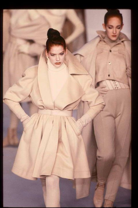 A white monochrome minimal outfit: White generous swing coat narrow sleeves and standing collar with a slim waist gather by a large leather belt over a white turtleneck by Claude Montana, fall 1987