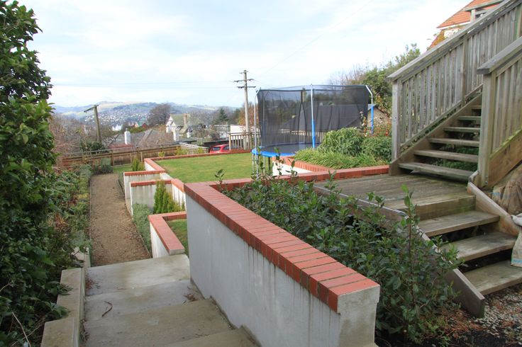 A series of retaining walls has been used to provide a level lawn for a social area and an area of play for children.