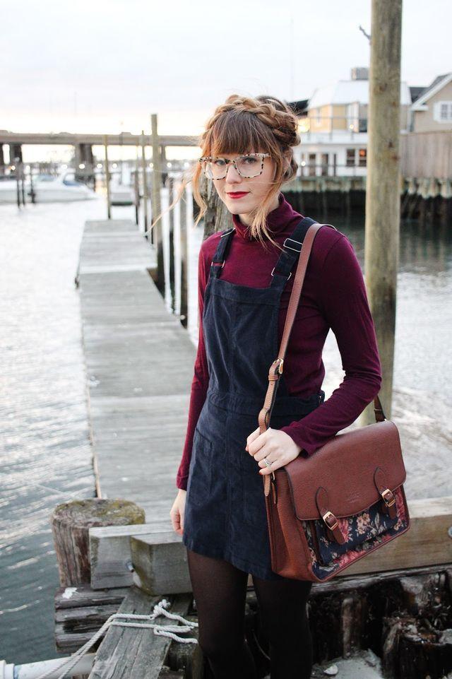 Burgundy turtleneck long-sleeved shirt, navy corduroy dress overalls, tights, glasses