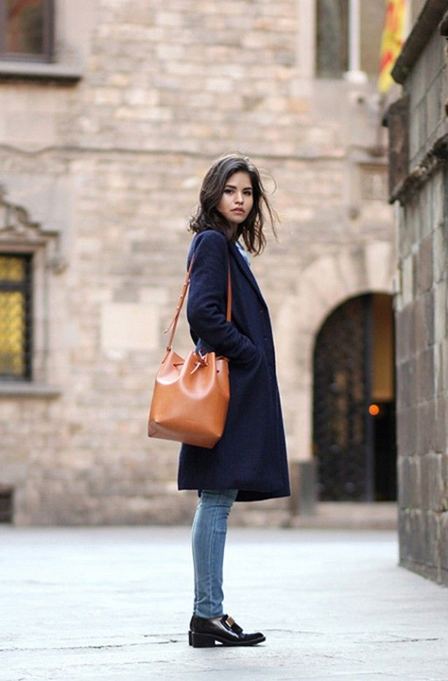 A navy coat is paired with easy skinny jeans, loafers, and a brown leather bucket bag