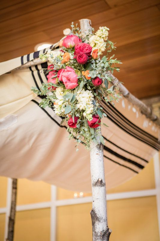 A birch tree wood chuppah draped with striped linens and decorated with pink peony floral arrangements for a shabby chic rustic indoor wedding. | J&M Floral and Event in New Jersey
