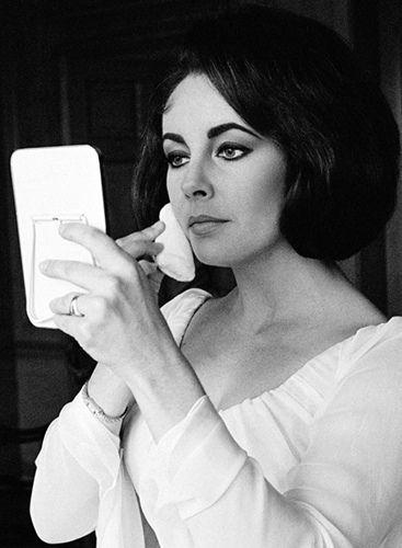 Elizabeth applies her make-up, whilst filming 'Elizabeth Taylor in London' at the Dorchester, July 1963