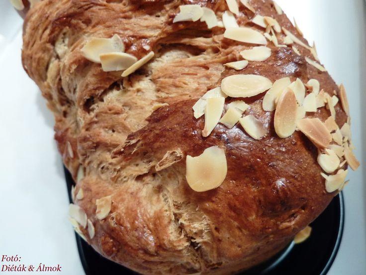 kalács -  Hozzávalók:      25 dkg teljes kiőrlésű tönkölyliszt     25 dkg fehér tönkölyliszt     1 tojássárgája     6 dkg nyírfacukor/eritrit     1 csipet só     3,5 dkg élesztő     2,8 dl langyos tej     1 tk. cukor     1,5 dkg átszitált, cukrozatlan kakaópor     1 tojásfehérje     1 dkg szeletelt mandula (elhagyható)