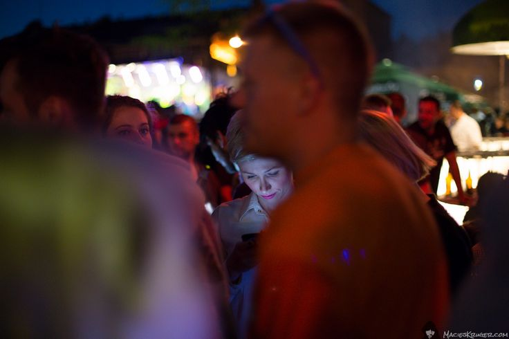 "#Beautiful, #magical #shot of a #woman with a #smartphone between people at the event ""#Night of Praga"" (#Noc Pragi) in #Warsaw #Vodka Distillery Koneser (Warszawska Wytwórnia Wódek Koneser). #City #Warszawa #Poland #Polska"