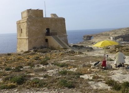 Tom Forrestall sketching the Dwerja Tower, on Gozo, Malta. The iconic Azure Window, visible on the right, no longer exists. Photo by Monica Forrestall