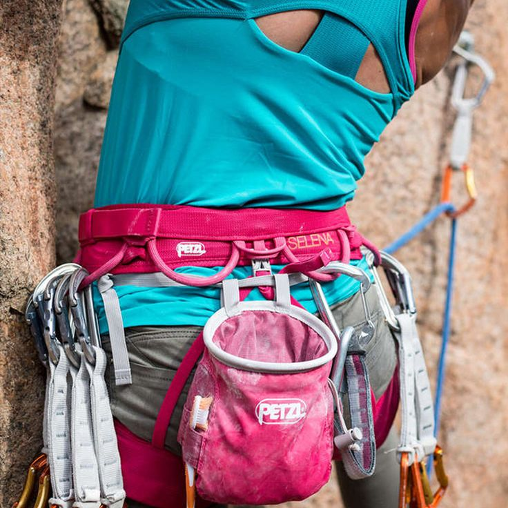 A woman lead climbs an outdoor route with a Raspberry Petzl Selena Climbing Harness and chalk bag.