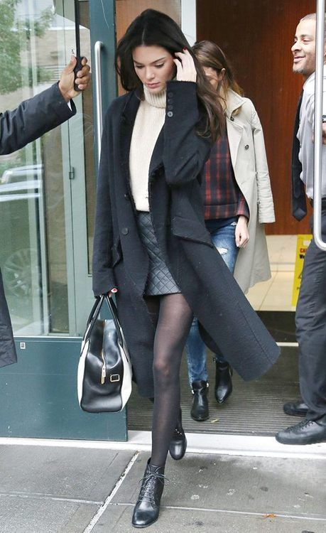 Kendall Jenner wears a beige turtleneck styled with tights and a mini skirt, paired with a charcoal gray trenchcoat
