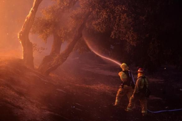Firefighters spray water near a burning house in the Twin Pines Road area at the Silver Fire near Banning, California August 7, 2013.