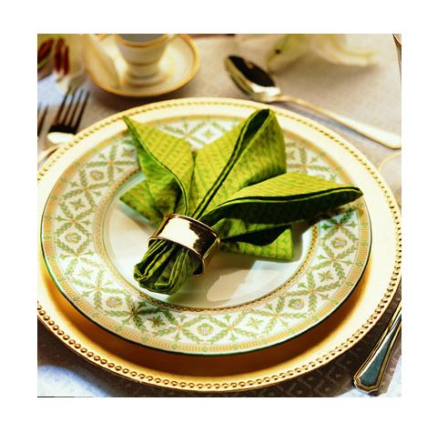Slip the napkin ring onto the rolled napkin to hold it in place. Turn the napkin over so that the rolls are on the bottom and the smooth napkin surface shows on the top. Put your rolled napkin in place on the table.