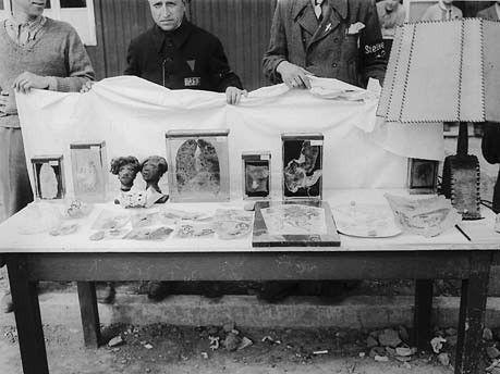 """kz buchenwald Ein Lampenschirm aus Menschenhaut, Schrumpfköpfe, eingelegte Organe: Ehemalige Häftlinge hinter einem Tisch mit """"Exponaten"""" der SS-Pathologie.  Foto: National Archives, Washington"""
