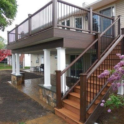 Decks Only Custom Designed and Built 2nd floor deck with dry space underneath and Cambridge ledgstone patio.