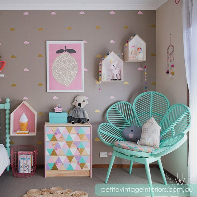 Girls bedroom with a brown wall behind features an assortment of pink, yellow, and brown three inch cloud wall decals. A chic teal chair shaped like a flower in the corner of the room.