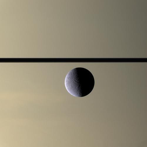 Rhea, with Saturn and rings in background, as seen by the Cassini spacecraft