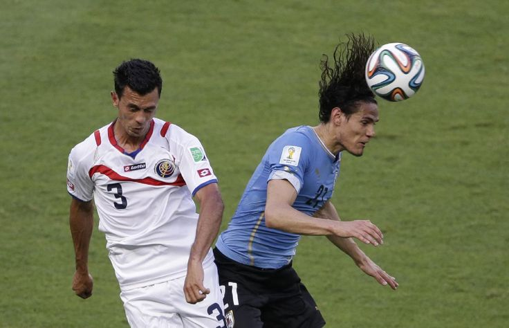 Costa Rica's Giancarlo Gonzalez, left, and Uruguay's Edinson Cavani go for a header during the group D World Cup soccer match between Urugua...