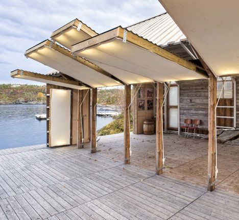 Naust paa Aure by TYIN tegnestue Architects. A timber summer house in Norway where flaps open the interior onto a deck.