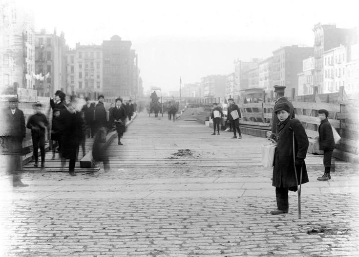 """A one-legged newspaper boy and other """"newsies"""", on Delancey Street, on December 26, 1906."""