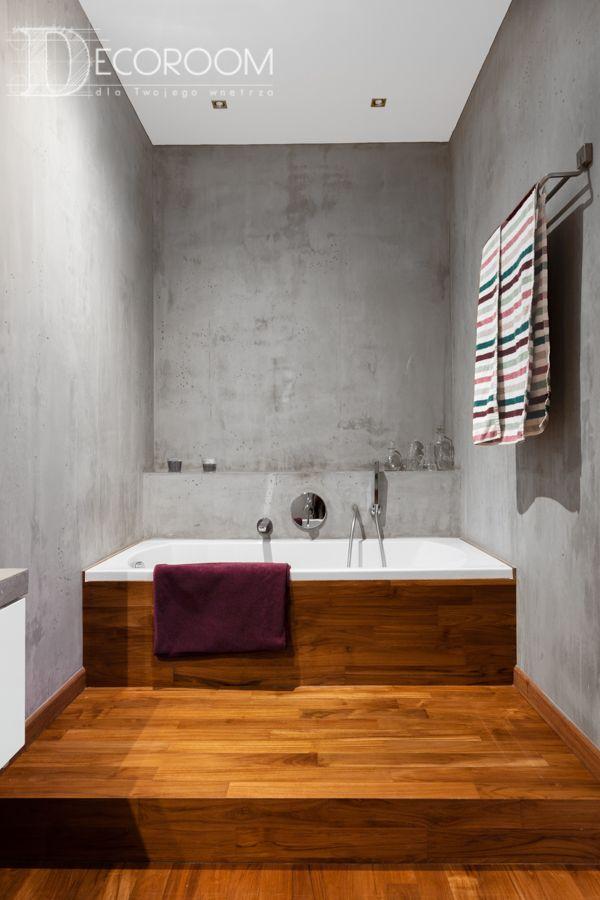 Łazienka w mieszkaniu na Woli została wykończona bez użycia ani jednej płytki. Łączy w sobie drewno i beton architektoniczny. Wanna umieszczona na podeście tworzy idealne miejsce na długie kąpiele.
