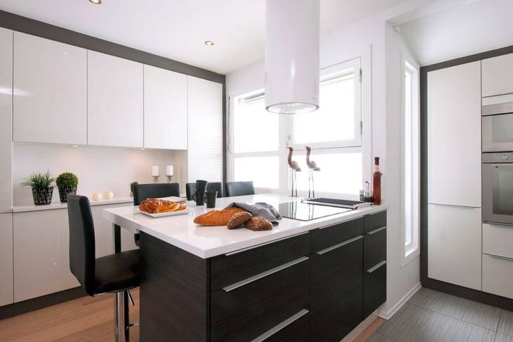 Kjøkkenet er enkelt og stilrent med en stor kjøkkenøy som fungerer som både arbeidsbenk og spisebord.