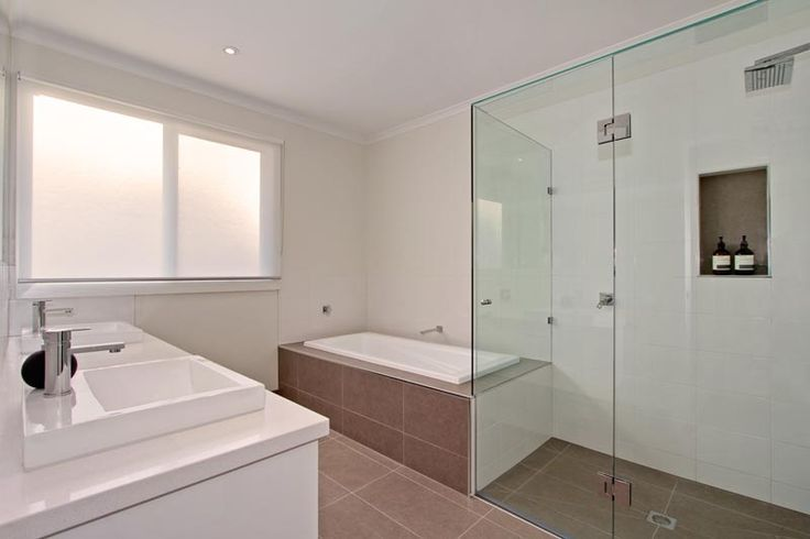 The bathroom is simple yet boasts character with the organic coloured tiles, large glass shower and white cabinets.
