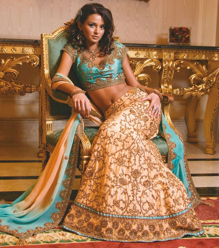 Peach A line lengha stylised with contrast bordes compiled with turquoise embroidery. Blouse is elegantly set with antique kundan work and shaded