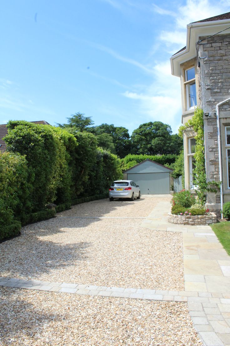 Long gravel driveway edged by a sweeping limestone path to