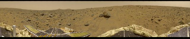 """This is the first contiguous, uniform 360-degree color panorama taken by the Imager for Mars Pathfinder (IMP) over the course of sols 8, 9, and 10 (Martian days). Different regions were imaged at different times over the three Martian days to acquire consistent lighting and shadow conditions for all areas of the panorama. At left is a lander petal and a metallic mast which is a portion of the low-gain antenna. On the horizon the double """"Twin Peaks"""" are visible, about 1-2 kilometers away. The…"""