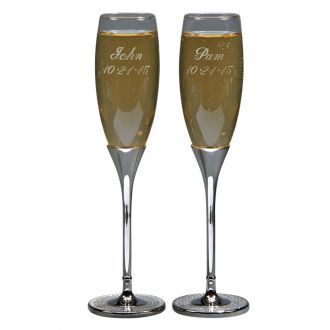 "These glass and metal toasting flutes feature the Glitter Galore look of acrylic covered crystals encased in bright, non-tarnishing, silver-colored metal in the base of each of the 2 flutes. The flute bowl is clear glass - to allow you to watch those champagne bubbles rise - while the stem and base are non-tarnishing silver-colored metal with the Glitter Galore feature. Each flutes measures just over 10"" tall overall. A great gift for the new couple to use to toast their families and…"