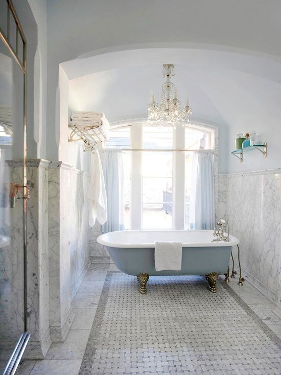 Blue claw foot tub, basket weave tiles, Carrera marble walls.