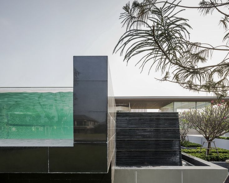office at floats transparent box over stone formations for the grand pinklao project